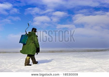 Ice Fisherman going away. Ice fishing - very popular winter hobby in Estonia, Latvia, Lithuania, Russia etc.