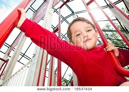Young boy playing on playground during spring.