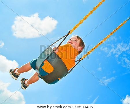 Cute young boy swings at park playground under natural sky