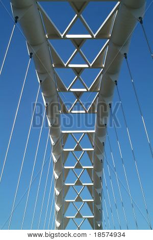 The arc of a modern suspension bridge stands against a clear blue sky in Toronto, Ontario, Canada.