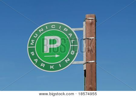 A generic green P directs drivers to a parking lot.