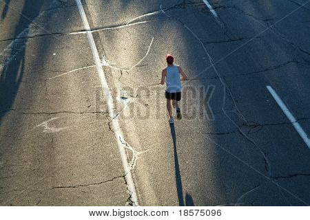 A lone marathon runner heads towards the rising sun during the opening stages of a race.
