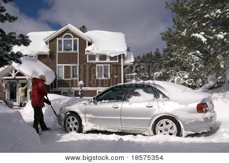 A couple digging out their car after a major snowfall.