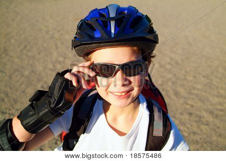 A nine year old boy wearing sunglasses, a bike helmet and a backpack crouches in a sunny park.
