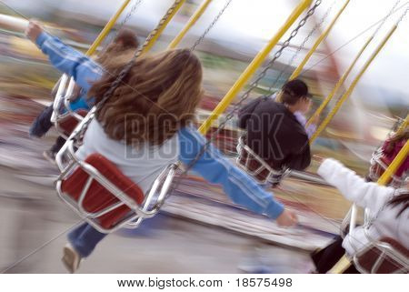 People riding fairground swings. (Shot with full motion blur.)