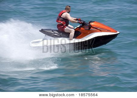 A man riding a late model jet boat. (The background has slight motion blur.)