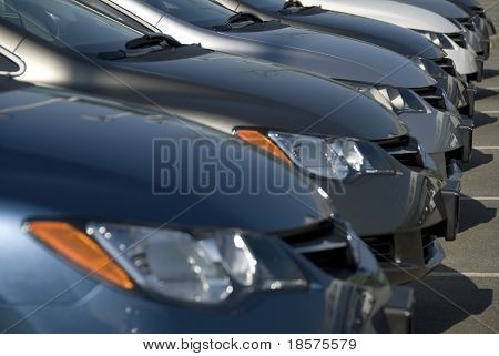 A lineup of new cars at a dealership. (Shot with minimum depth of field. Focus is on the third vehicle from the front.)