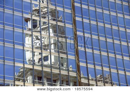 The clock of Chicago's Wrigley building reflected in a nearby office tower.
