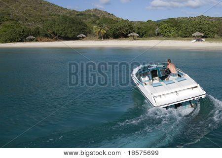 Ein Speedboot in das türkisfarbene Wasser der Karibik.
