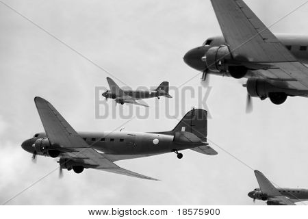 A flight of Dakota (Douglas C-47) transport planes banking to starboard. (Created with minimum depth of field. Focus is on the second aircraft from the front.)