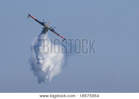A twin-engined water bomber dumping its load on a forest fire.