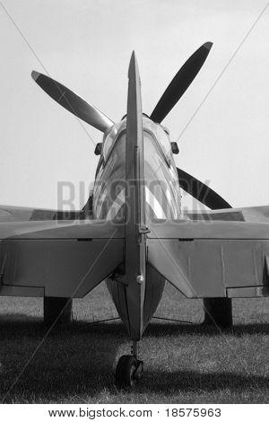 Tail of a mark IX British Spitfire parked beside a grass runway.