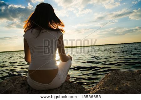 girl meditations in sunrays near water