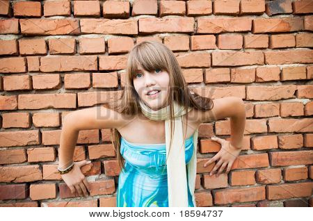 A young girl in dress by the wall
