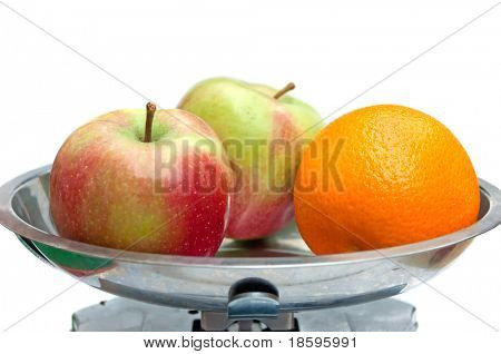 Two apples and orange on the libra