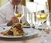 picture of flounder  - dinner of sauteed flounder and white wine with man eating in background - JPG