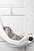 stock photo of newborn baby girl  - newborn baby sleeping in sling hung from door - JPG