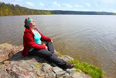 Overweight hiker woman relaxing and meditating on a cliff over lake. Active lifestyle and mental hea poster