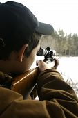stock photo of hunt-shotgun  - a teen boy hunting in the woods in winter - JPG