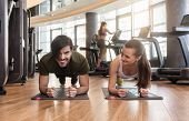Cheerful young couple exercising forearm plank side by side on mats during workout in the interior o poster