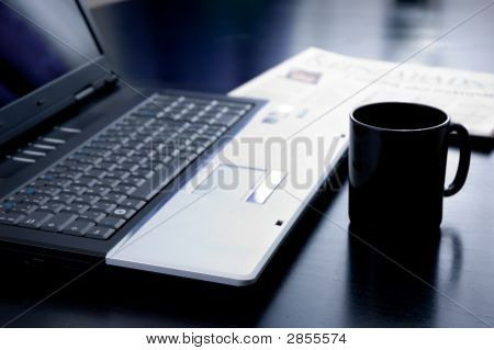 Still Life With Laptop Cup And A Newspaper