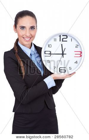 smiling businesswoman holding clock and shoving time