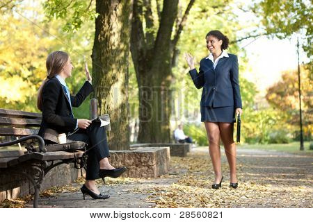 two young,  smiling business women meet in park