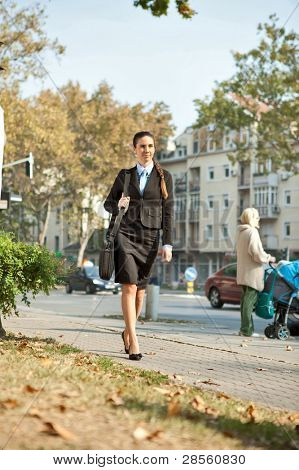 young  businesswoman walking on street in urban city