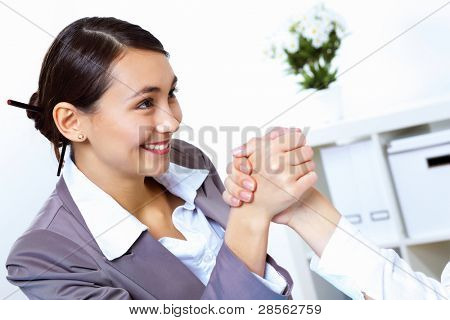 Two young women in business wear arm wrestling in office