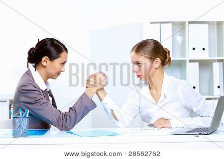 Two young women in business wear arm wrestling in office