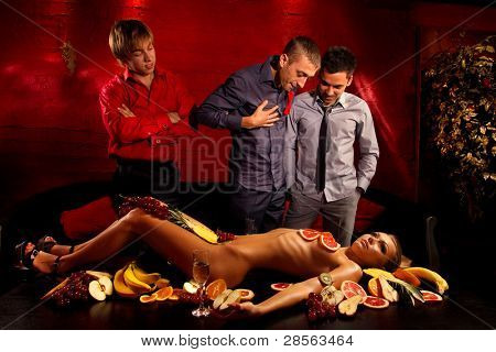 Guys having fun with woman decorated  by fruits
