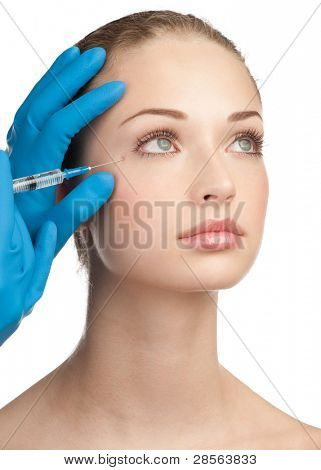 Close-up shot of cosmetic injection to the pretty female face. Isolated on white background