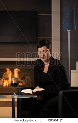 Young woman sitting in front of fireplace at home on a cold winter day, reading book.?
