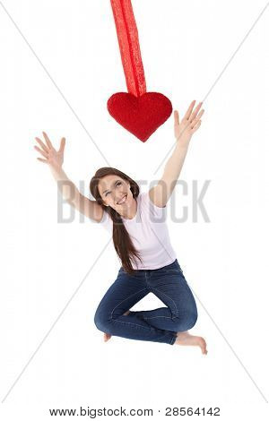 Pretty young woman reaching out for red heart, smiling.?