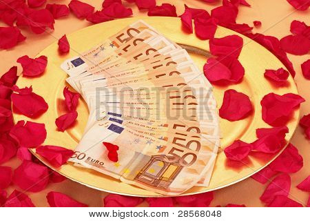 Fifty euro banknotes on a golden plate with rose petals