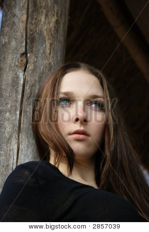 Teenage Girl In Black Near Old Timber Stock
