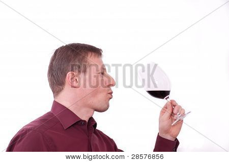 Man Is Tasting And Holding A Glass Of Red Wine