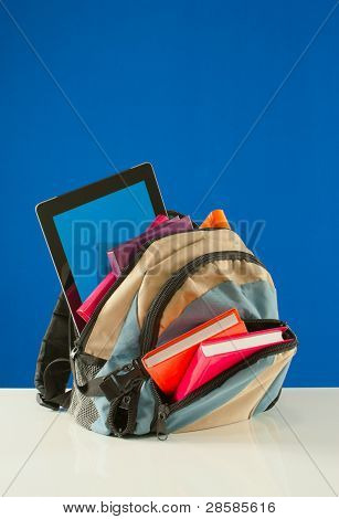 Backpack With Colorful Books And Tablet Pc On The Blue Background