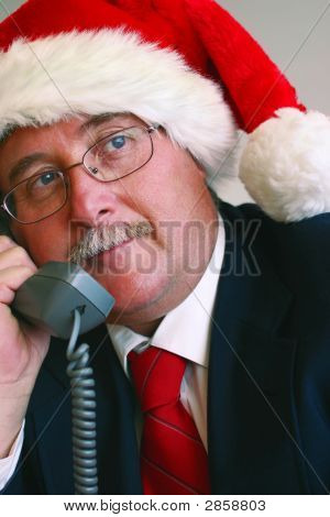 Businessman In Santa Hat Talking On Telephone