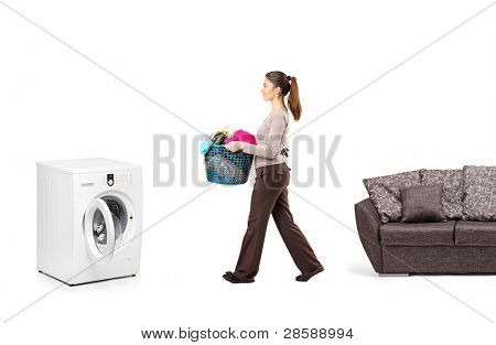 Full length portrait of a housewife holding a laundry basket and going towards a washing machine isolated on white background