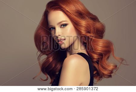 poster of Beautiful Model Girl With Long Curly Red Hair . Styling Hairstyles Curls .wavy Shiny Care