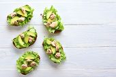 Tuna Sandwiches With Avocado And Lettuce Leaves Over Light Wooden Background With Copy Space. Tasty  poster