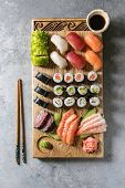 Sushi Set Nigiri Sashimi And Sushi Rolls On Wooden Serving Board With Soy Sauce And Chopsticks Over  poster