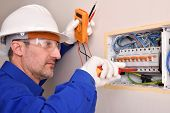 Electrical Installer With Protective Elements Working In An Electrical Panel Of A House. poster