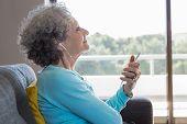 Peaceful Elderly Woman Wearing Earphones Enjoying Music. Side View Of Senior Grey Haired Lady Using  poster