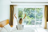 Woman waking up and stretching on bed in luxury hotel room in the morning. Sleeping well on comfy ma poster