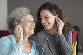 Happy Senior Woman And Her Daughter Listening To Music Together. Mother And Daughter Wearing Earphon poster