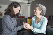 Positive Elderly Woman And Her Daughter Chatting And Holding Hands. Mother And Daughter Sitting On C poster