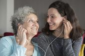 Positive Senior Lady And Daughter Listening To Music Together. Mother And Daughter Wearing Earphones poster
