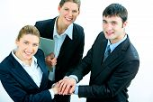 picture of joining hands  - Image of business people putting their hands on top of pile and looking at camera - JPG